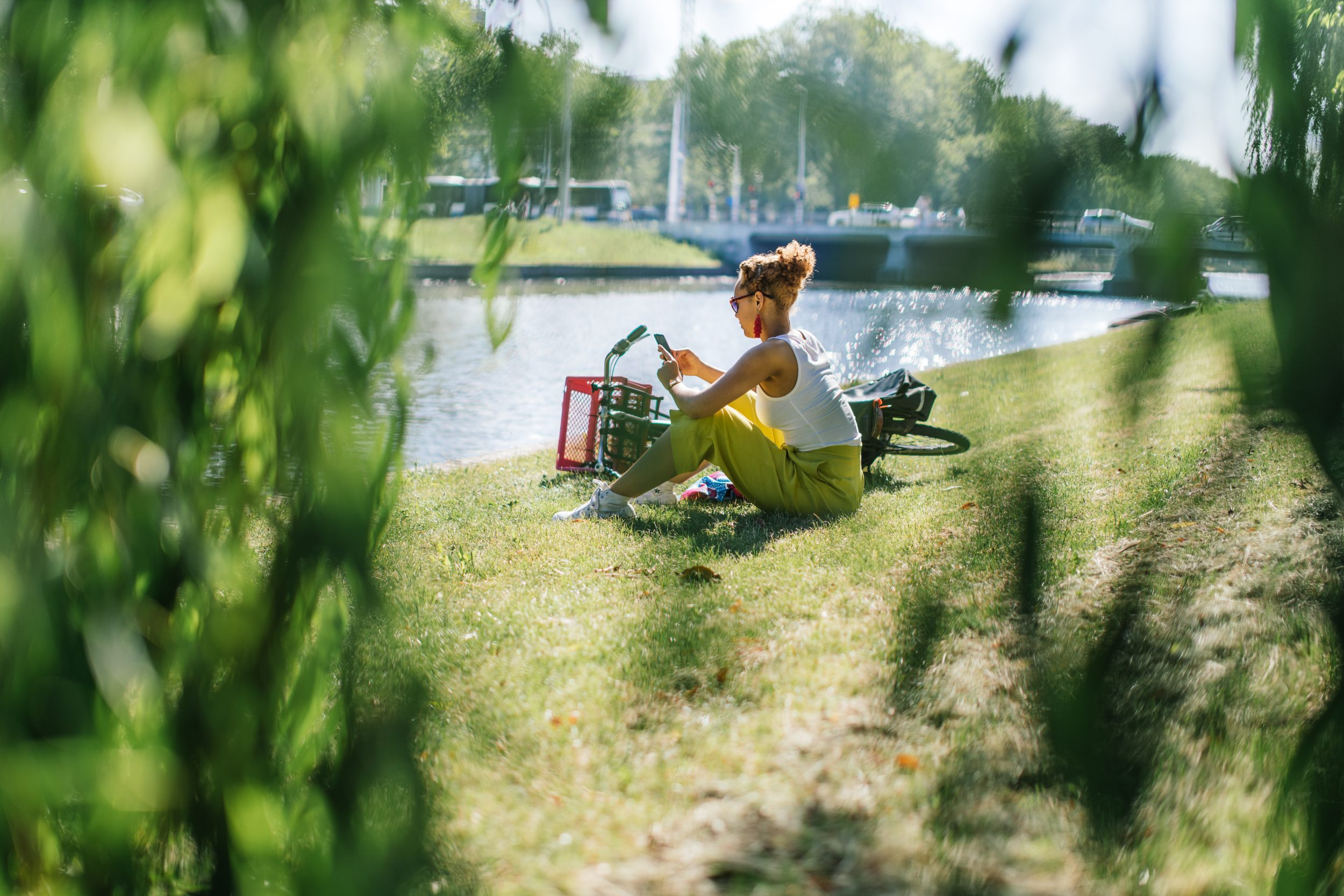 A woman sitting beside her bike on a grassy slope beside a canal.