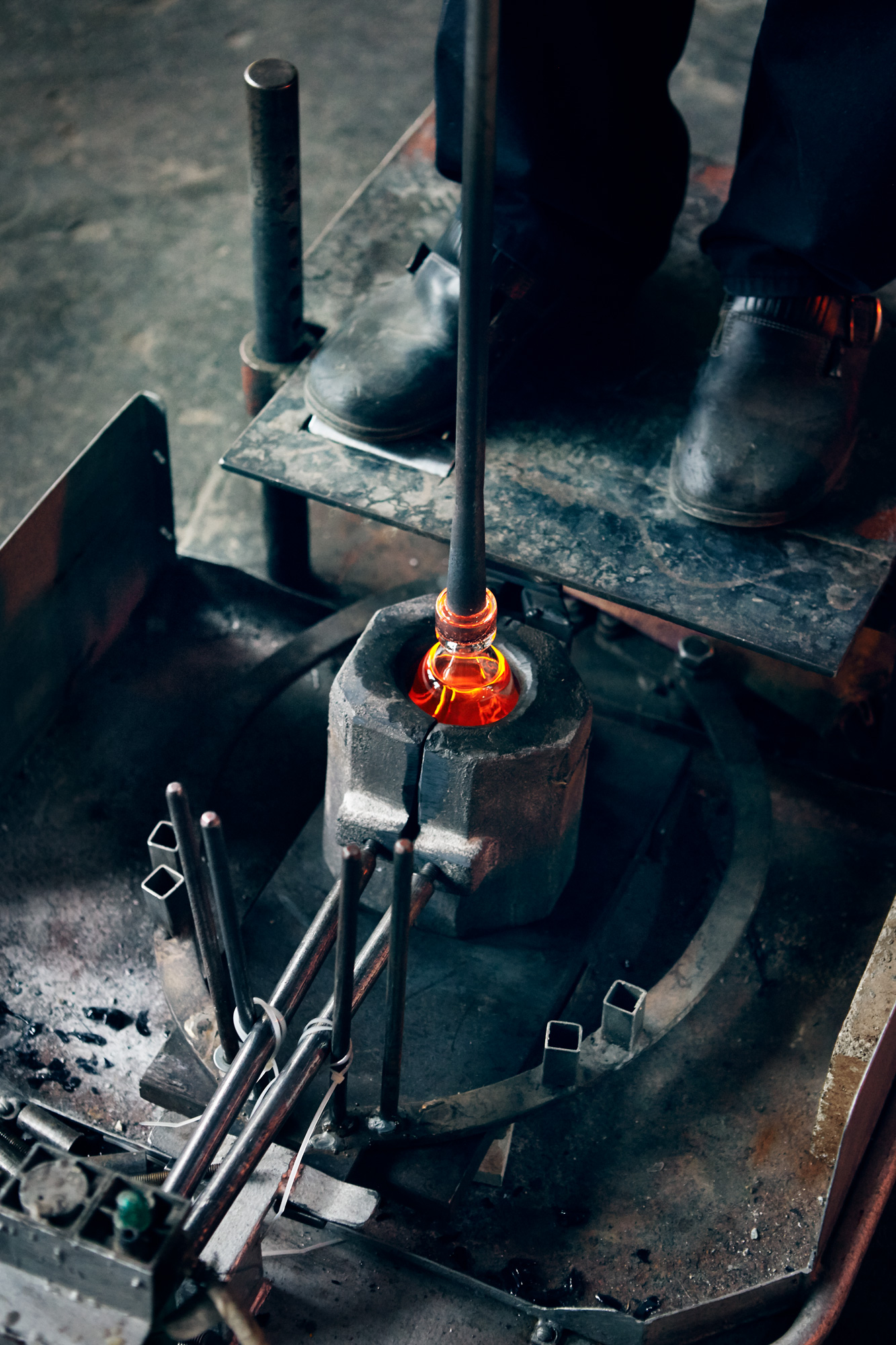 Molten glass on a blowpipe held into a mould.