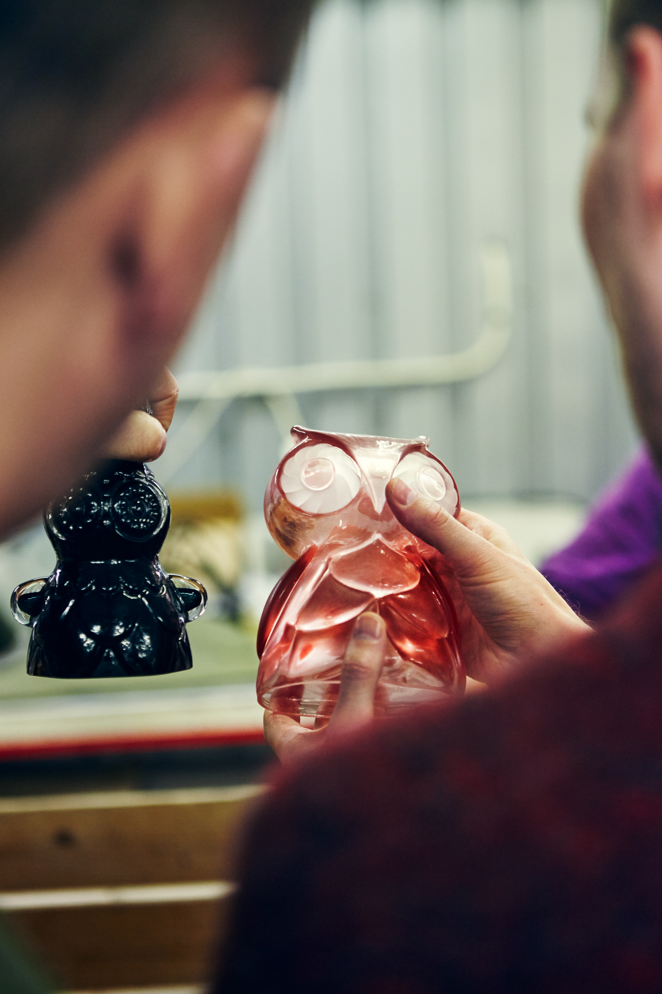 Two people inspecting coloured-glass figurines.