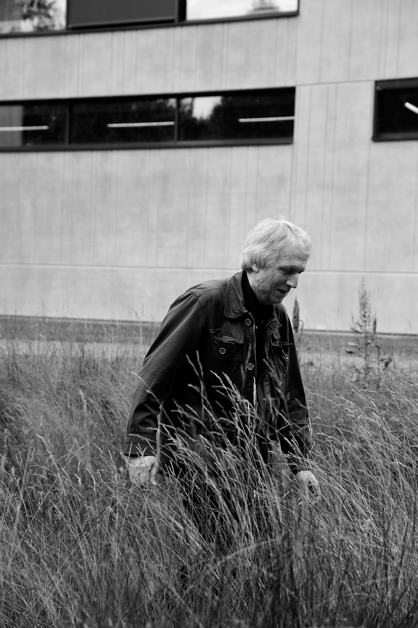 A man walking in high grass in front of a big building.