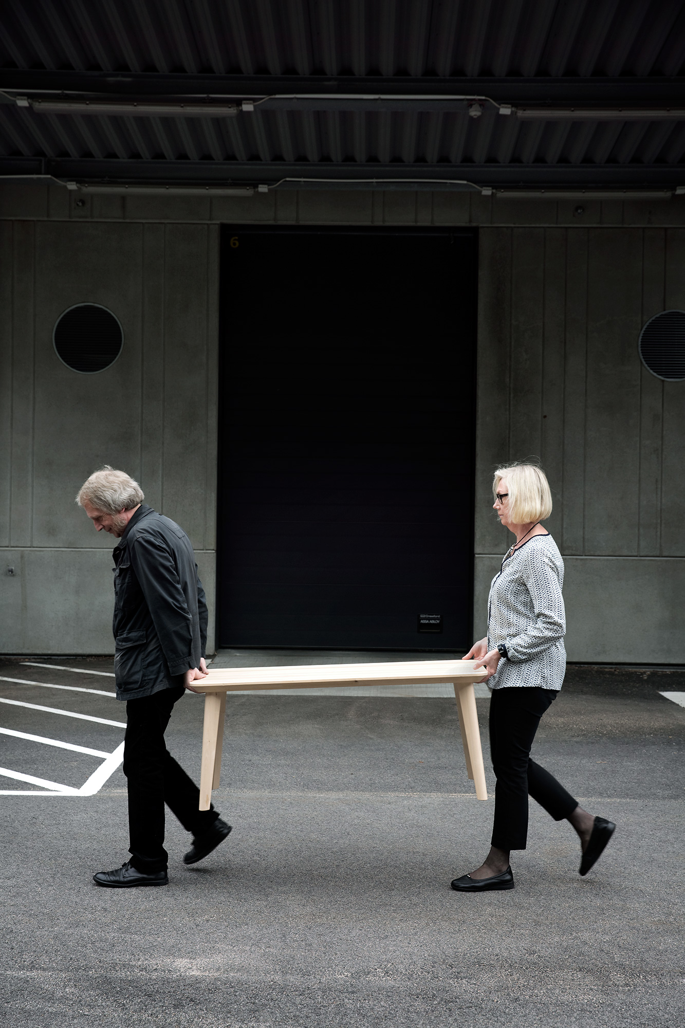 A man and a woman walking past a concrete facade, carrying a light wooden table between them.