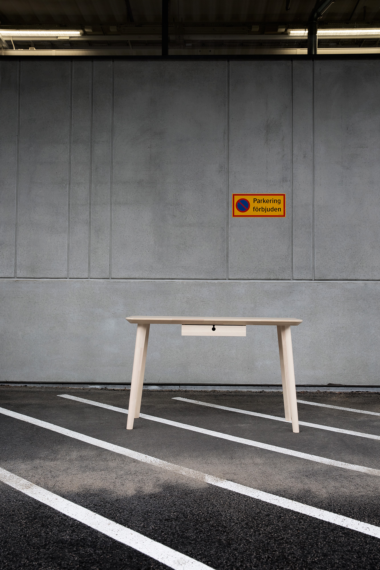 A light wooden table with a single drawer, standing on asphalt in front of a concrete facade with a parking-forbidden sign.