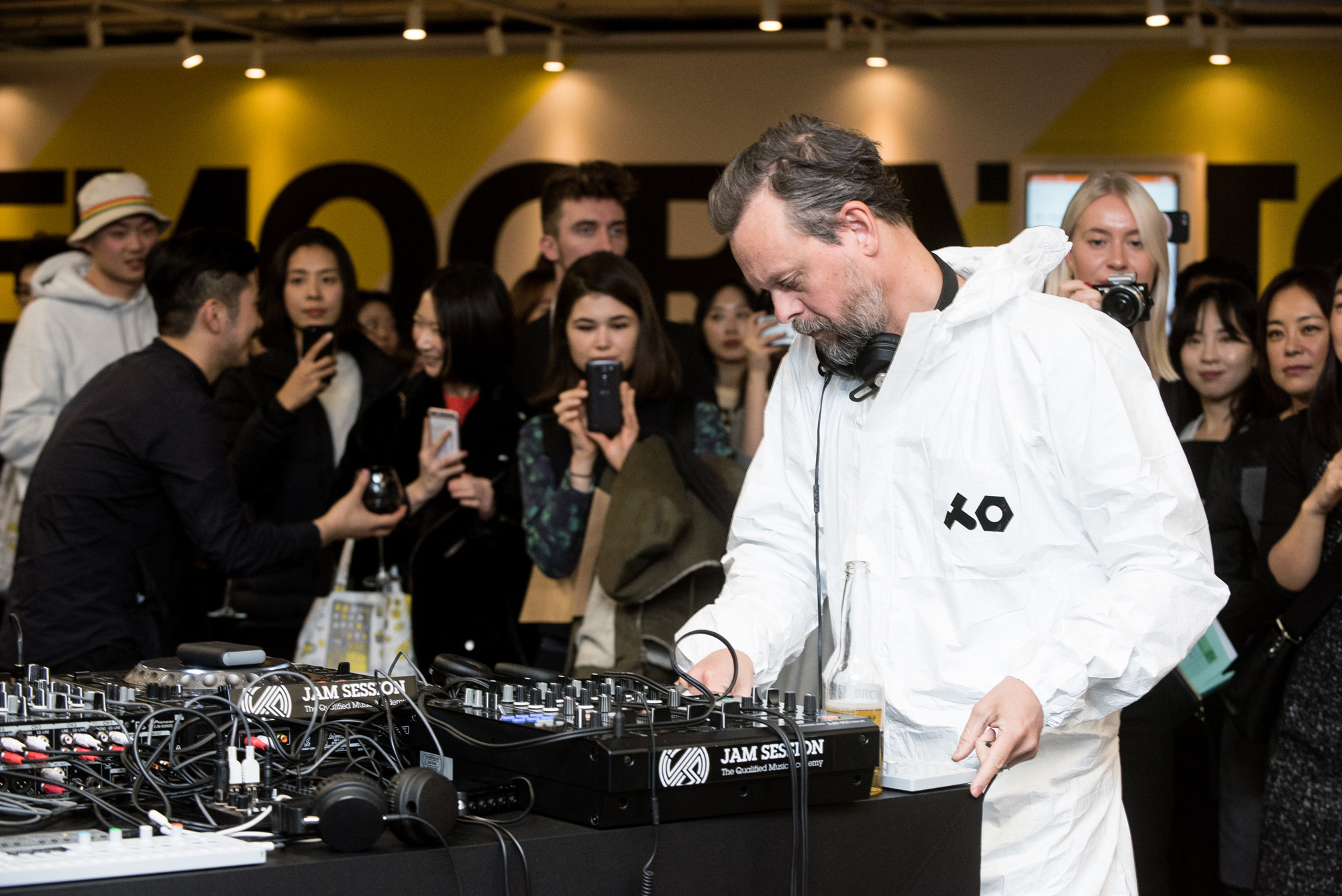 A DJ in a white jumpsuit works audio equipment before a crowd.