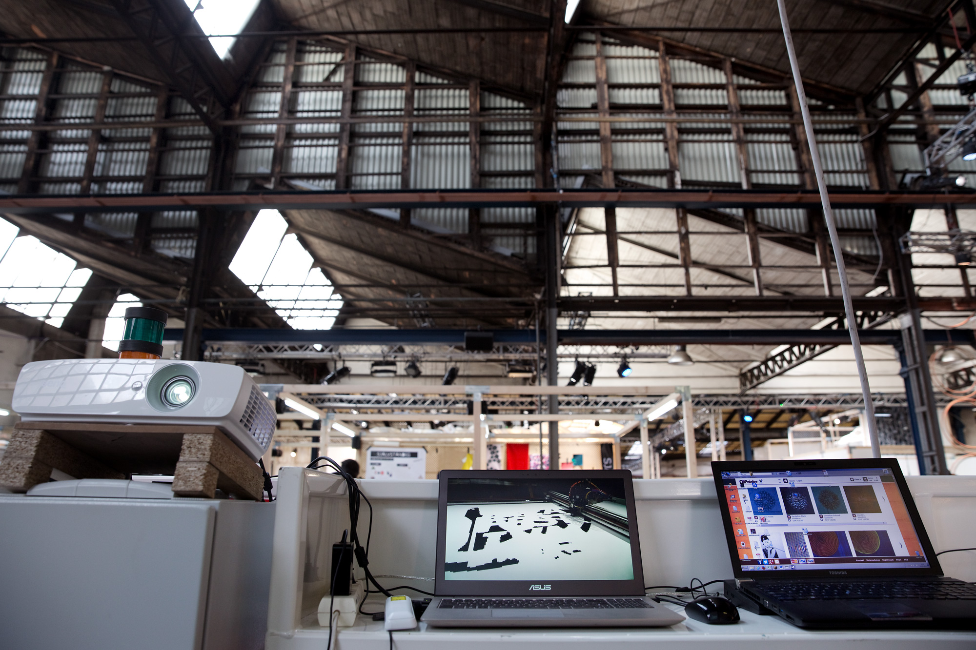 Two laptops and a projector on a table underneath a high ceiling in an industrial hall.