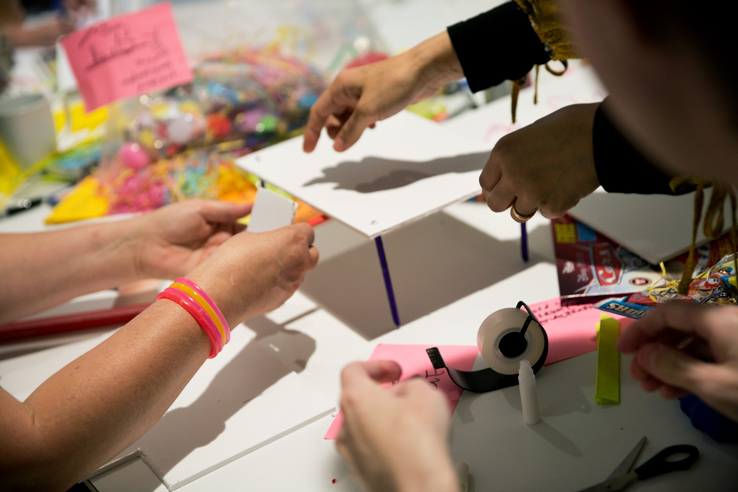 Hands working on a paper prototype. They are in action, gluing things together.