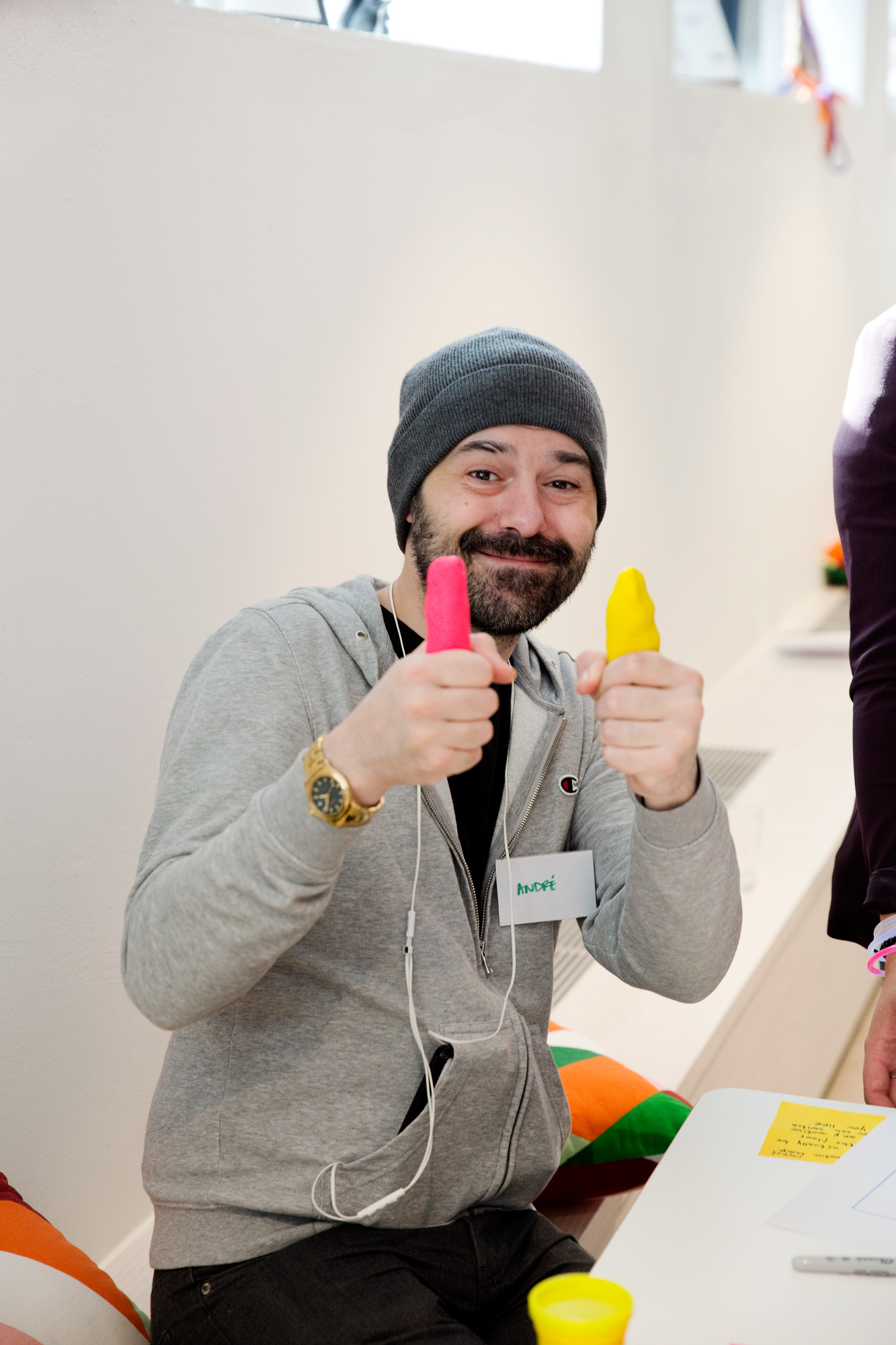 A man wearing a woollen hat holds two pieces of play dough, one yellow and one pink.