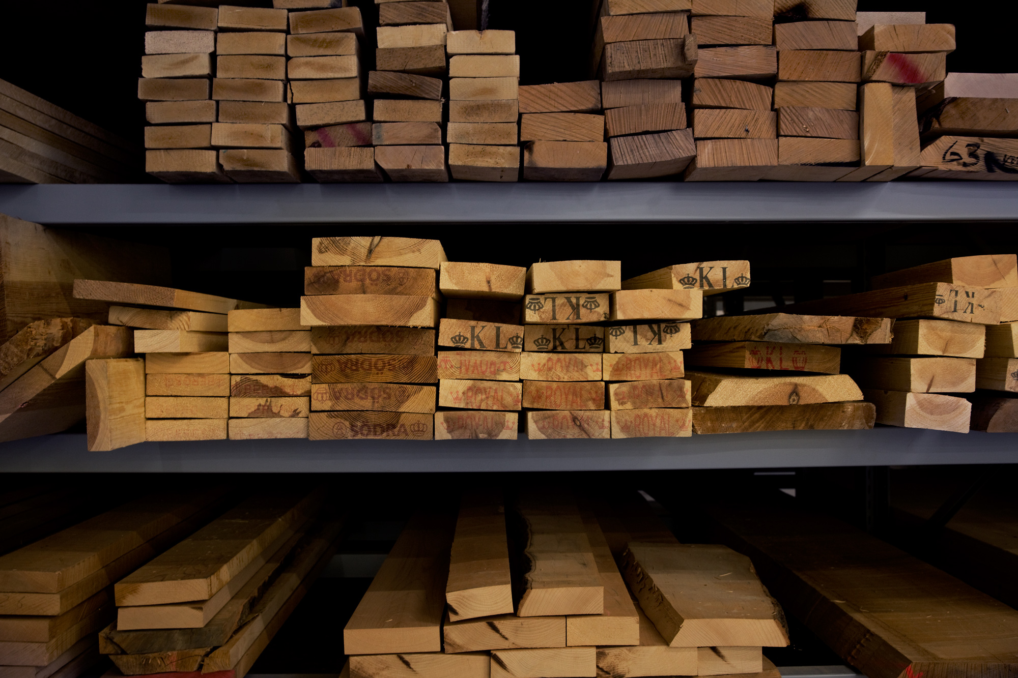 Planks of wood piled up on shelves.