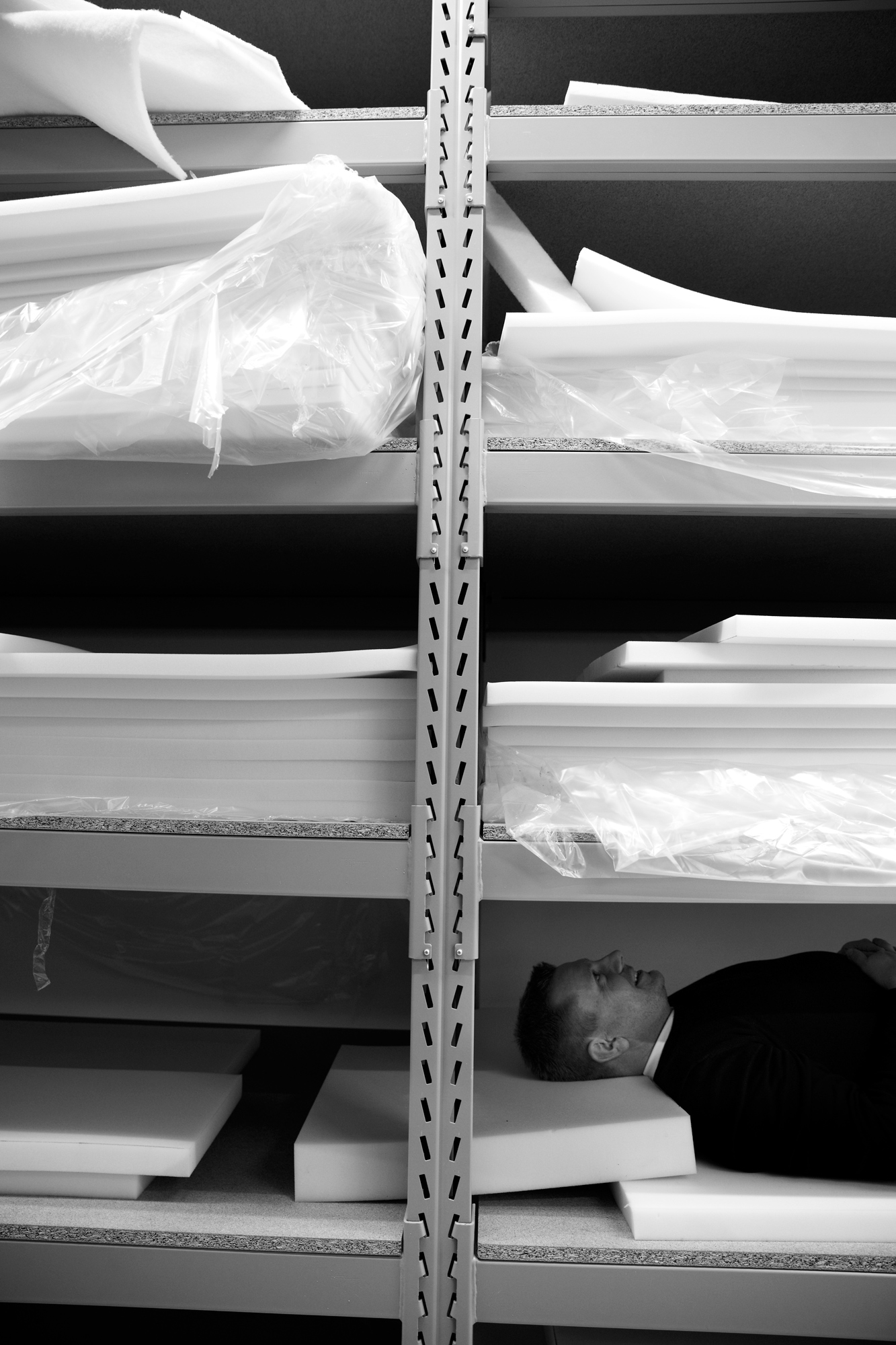 A man lying on mattresses, tucked into an industrial shelf otherwise filled with sheets of foam rubber.