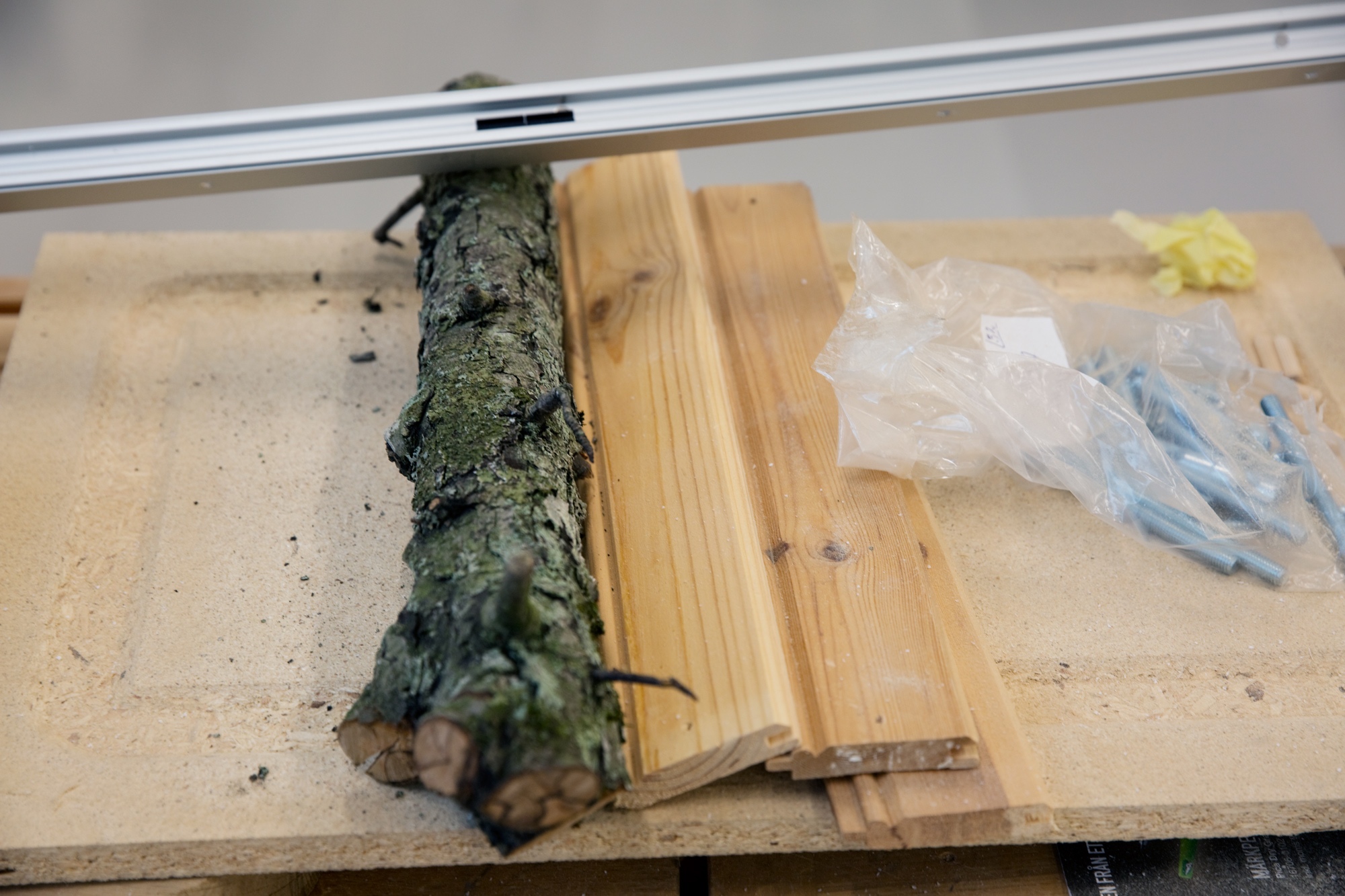 A tree branch, three short planks and plastic bags placed on a slab of chipboard.