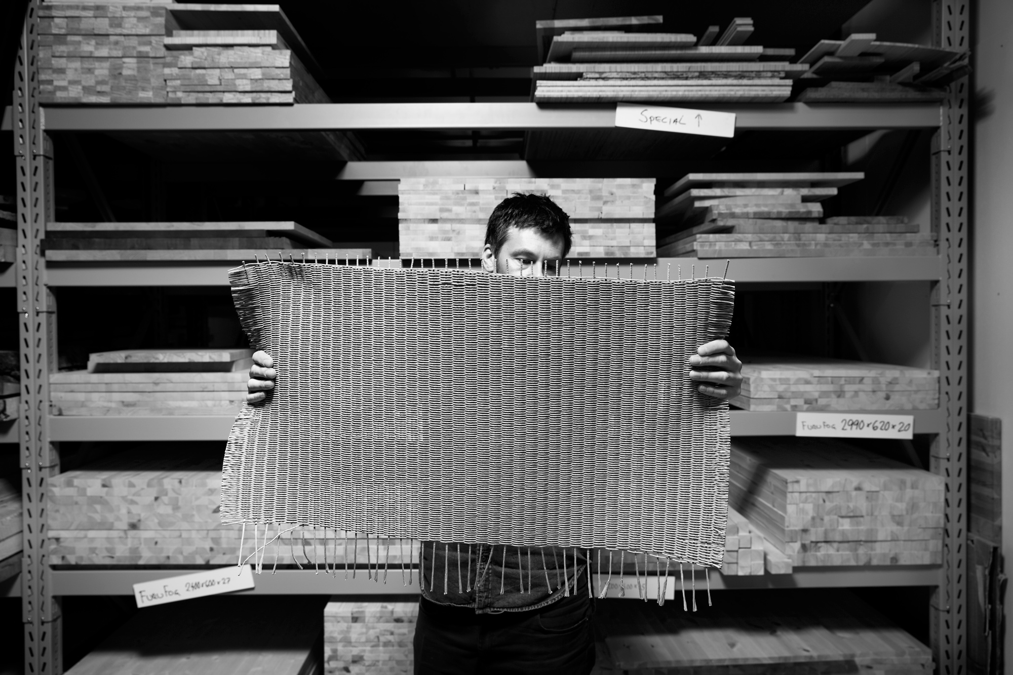 A man holding a sheet of woven material.