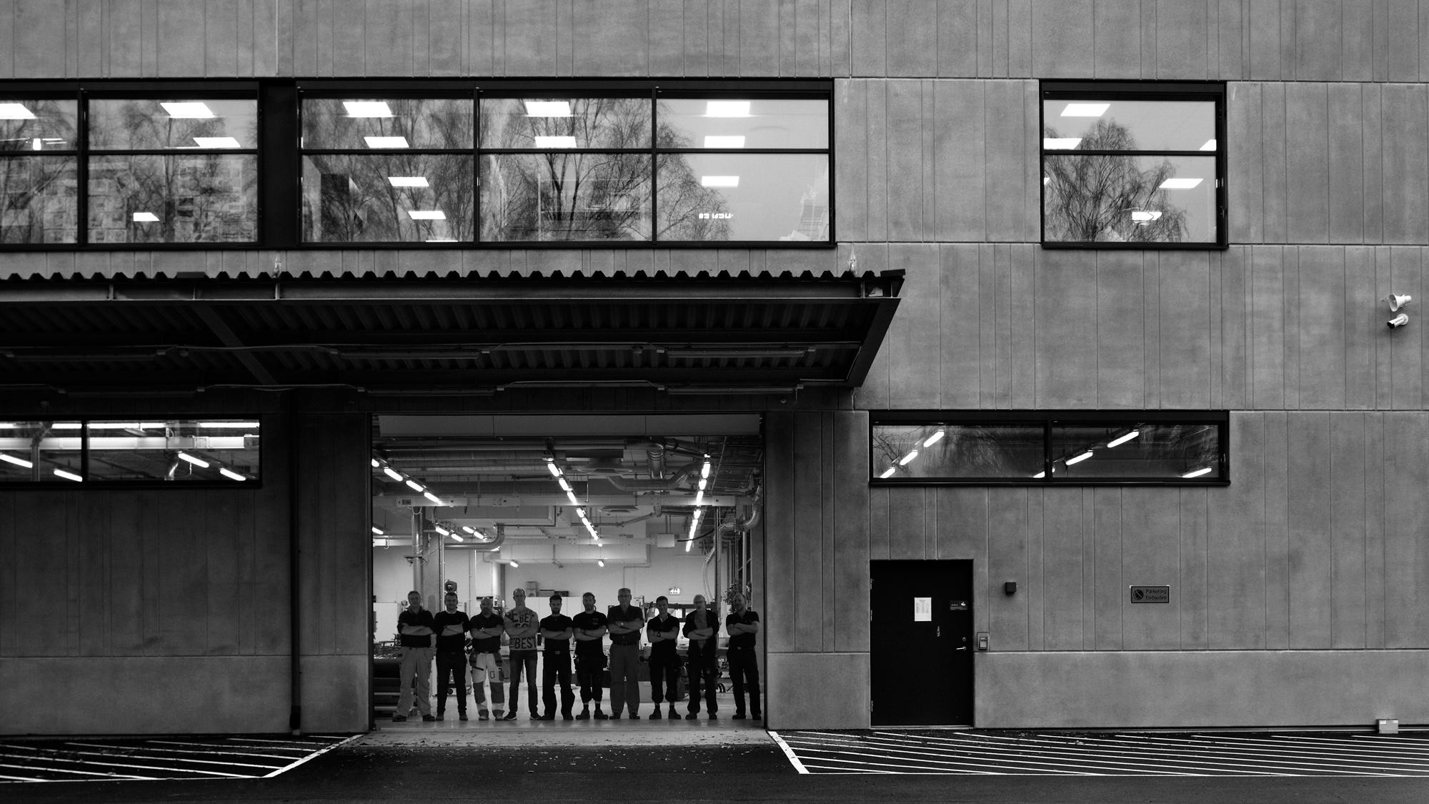 Ten men standing in an opening in the concrete facade of an industrial building.