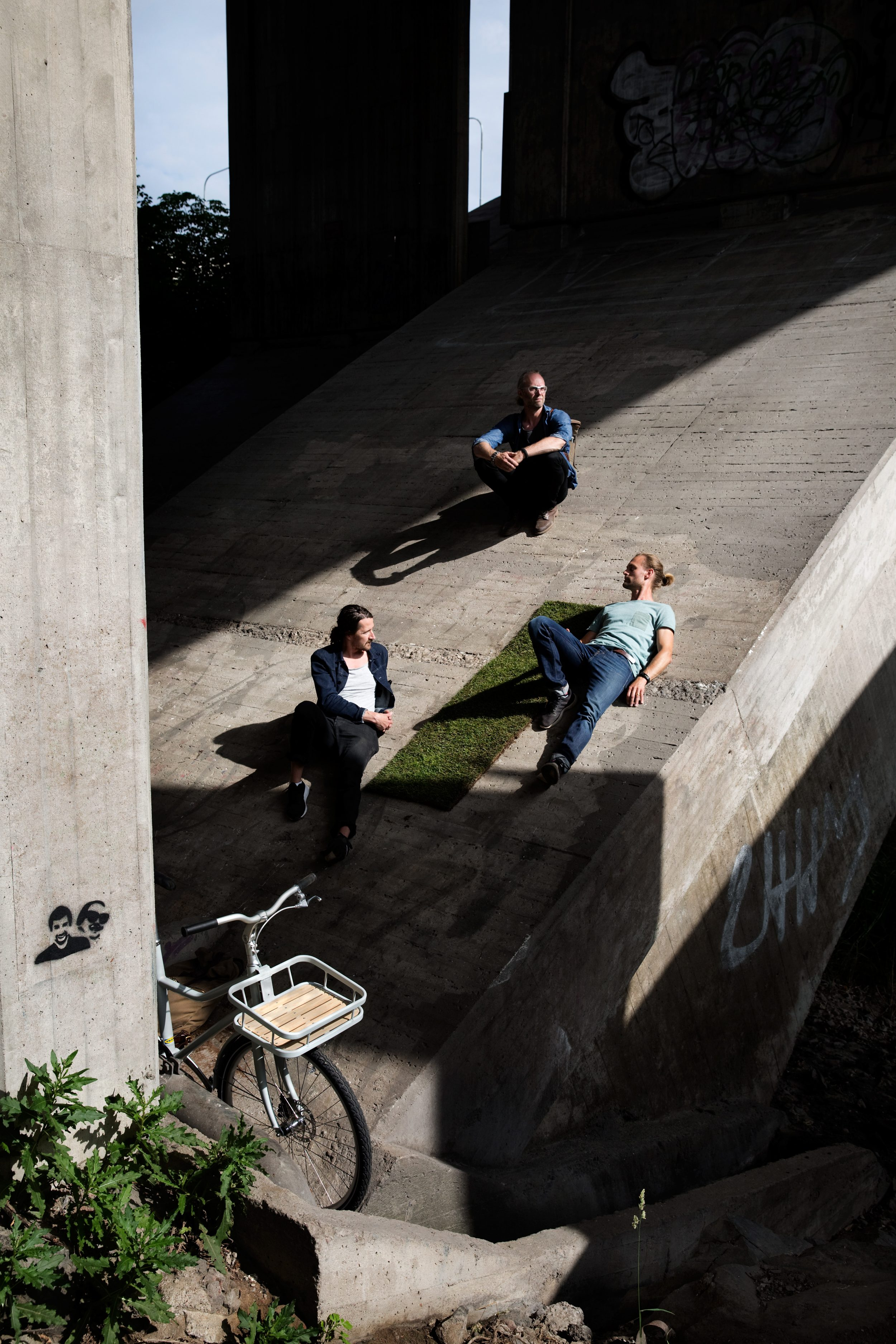Three men lounging on the concrete foundation of a bridge.