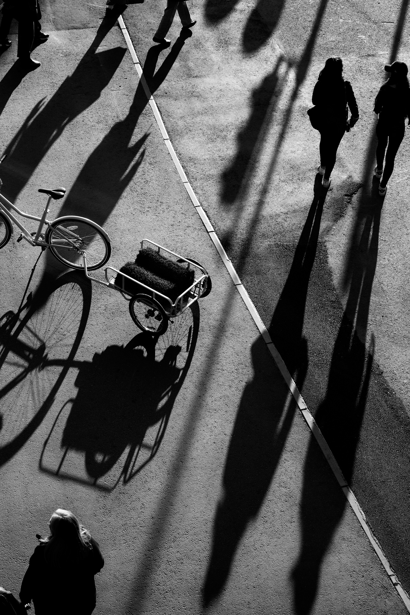 A streetscape in black and white, with a parked bicycle and walking people casting long shadows.