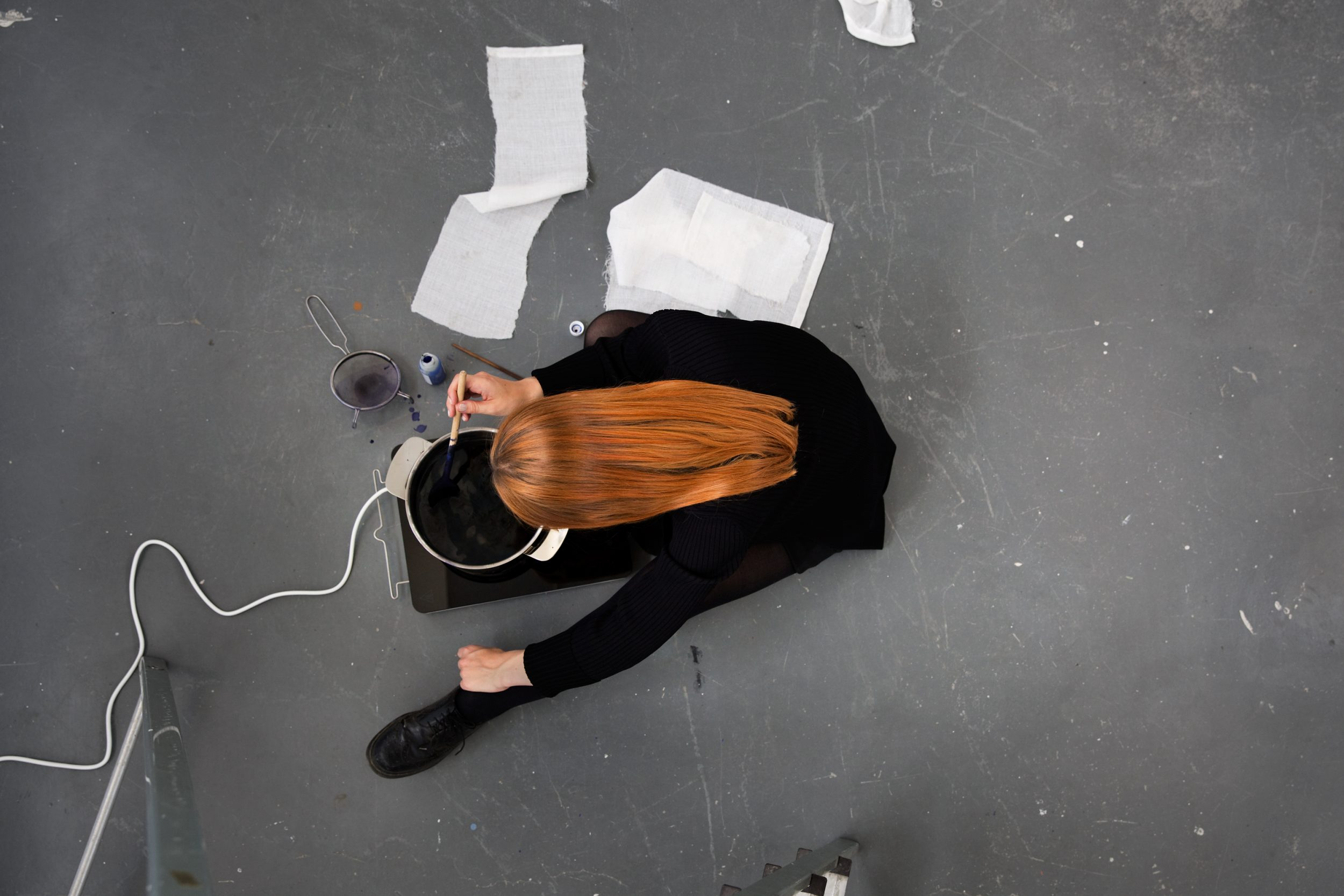 A woman with long red hair dressed in black sits on a floor, leaning over a pot placed on a portable hob.