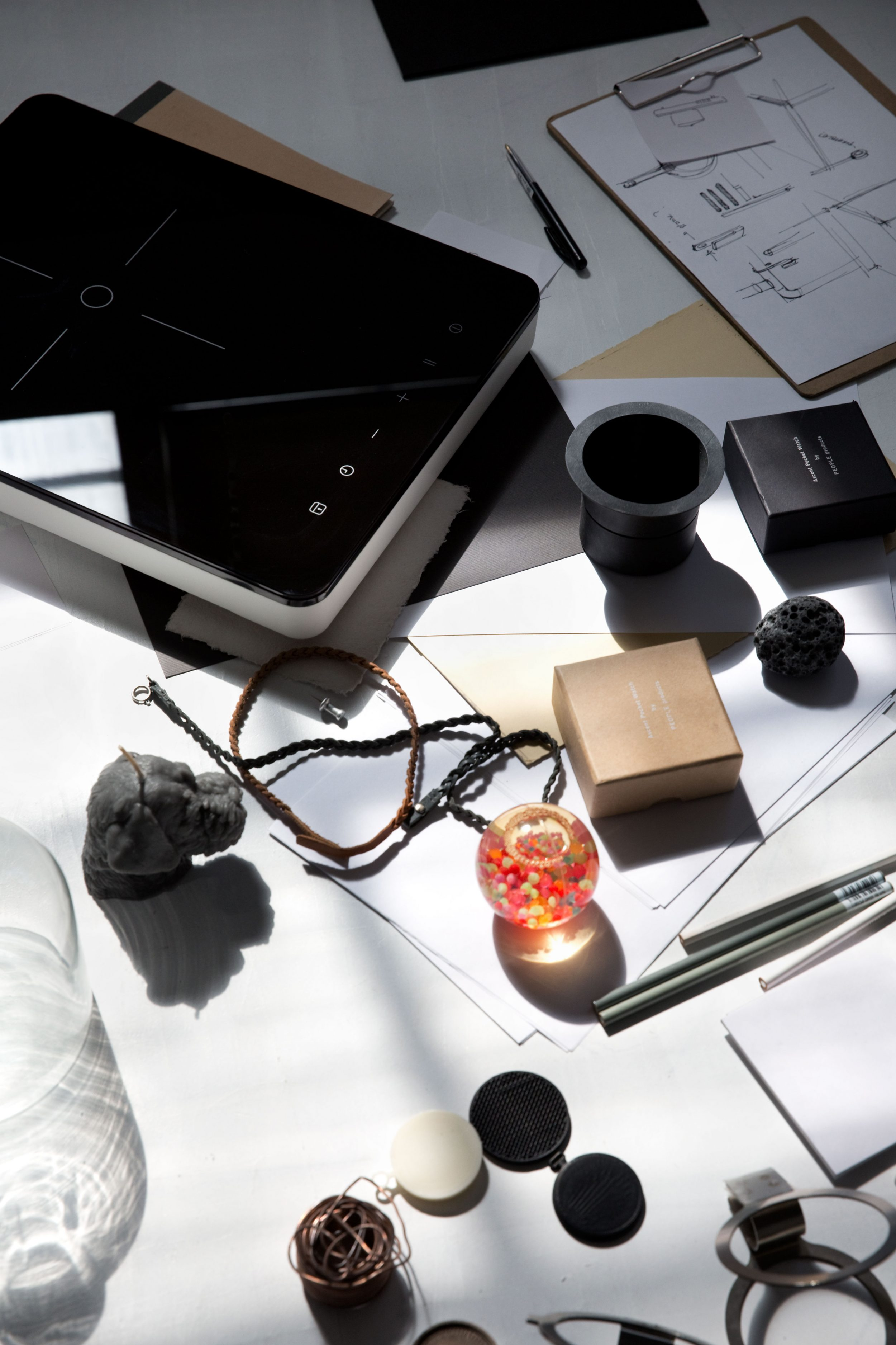 A portable induction hob placed on a desk filled with scattered paper and various objects.