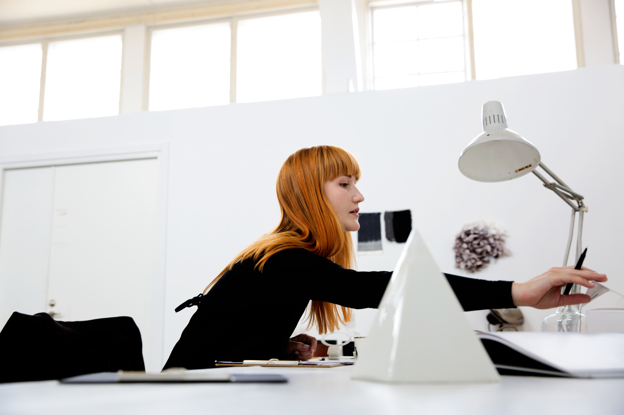 A red-haired woman in a black polo neck sits engrossed in work at a white desk in a white room with black details.