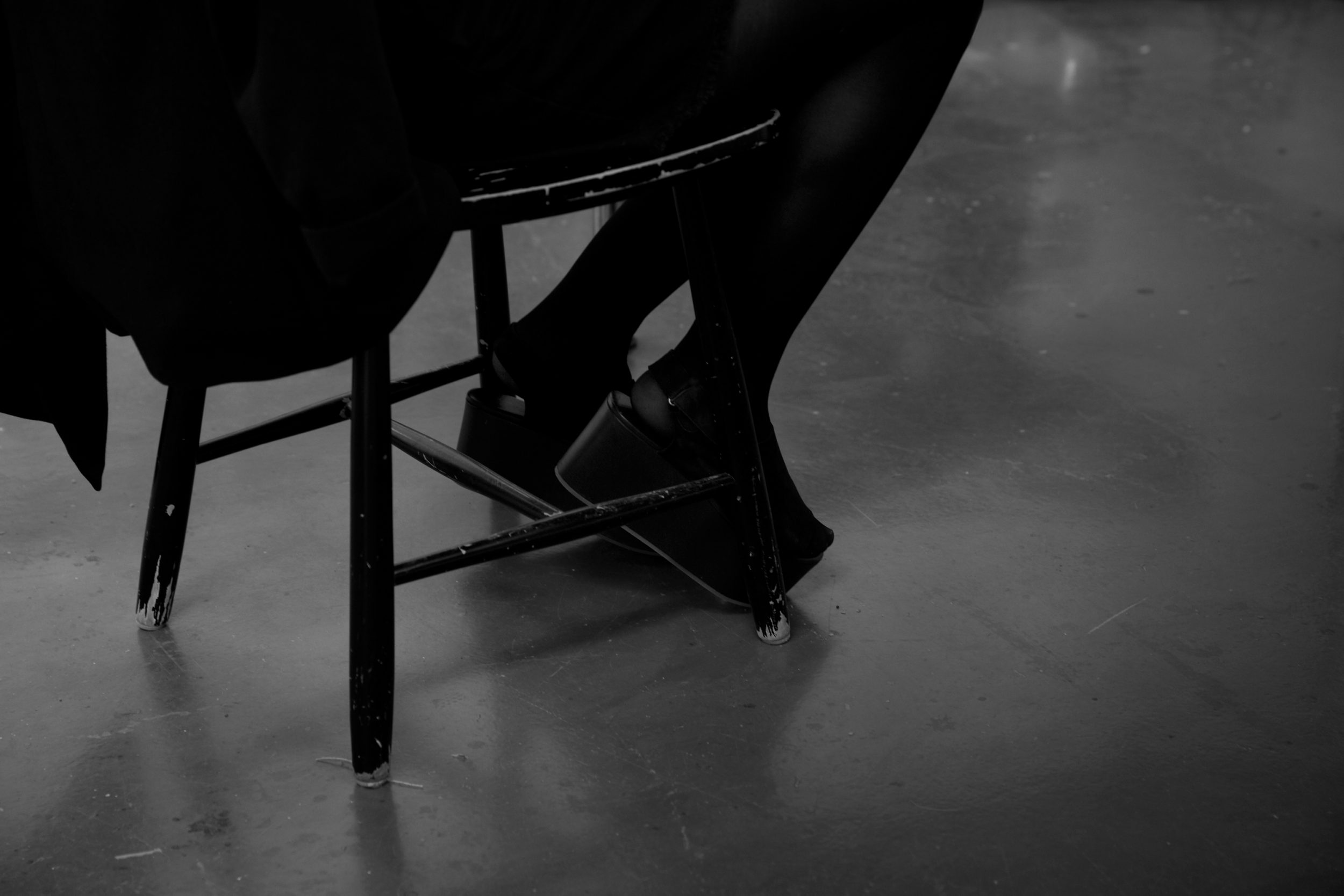 The black platform shoes of someone seated on a black wooden chair.