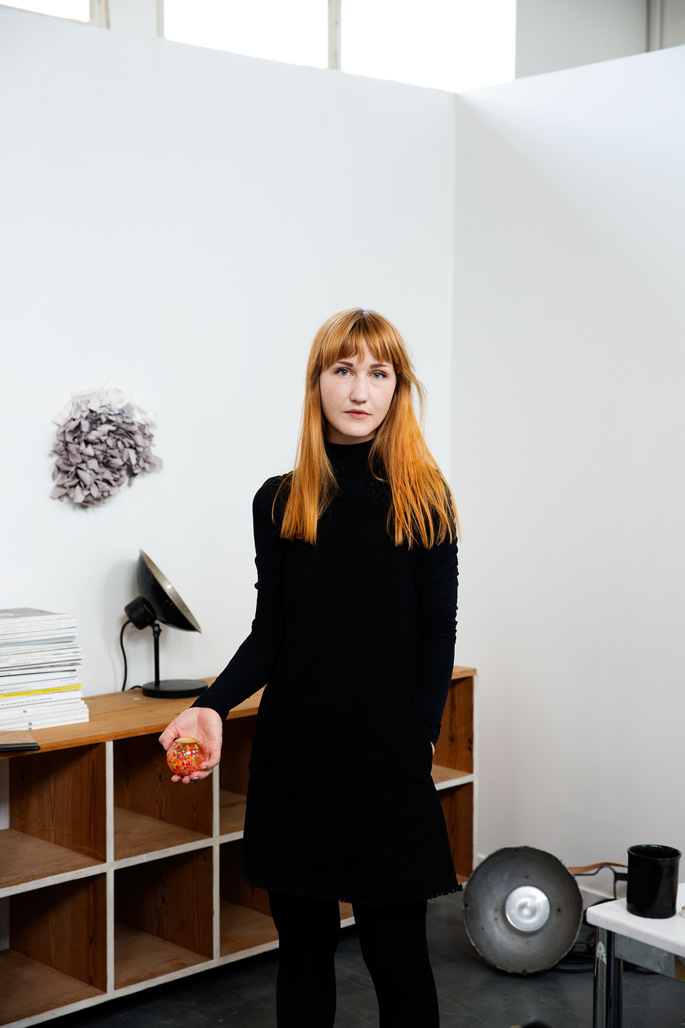A red-haired woman dressed in black stands between a desk and a sideboard in a space with white provisional walls.