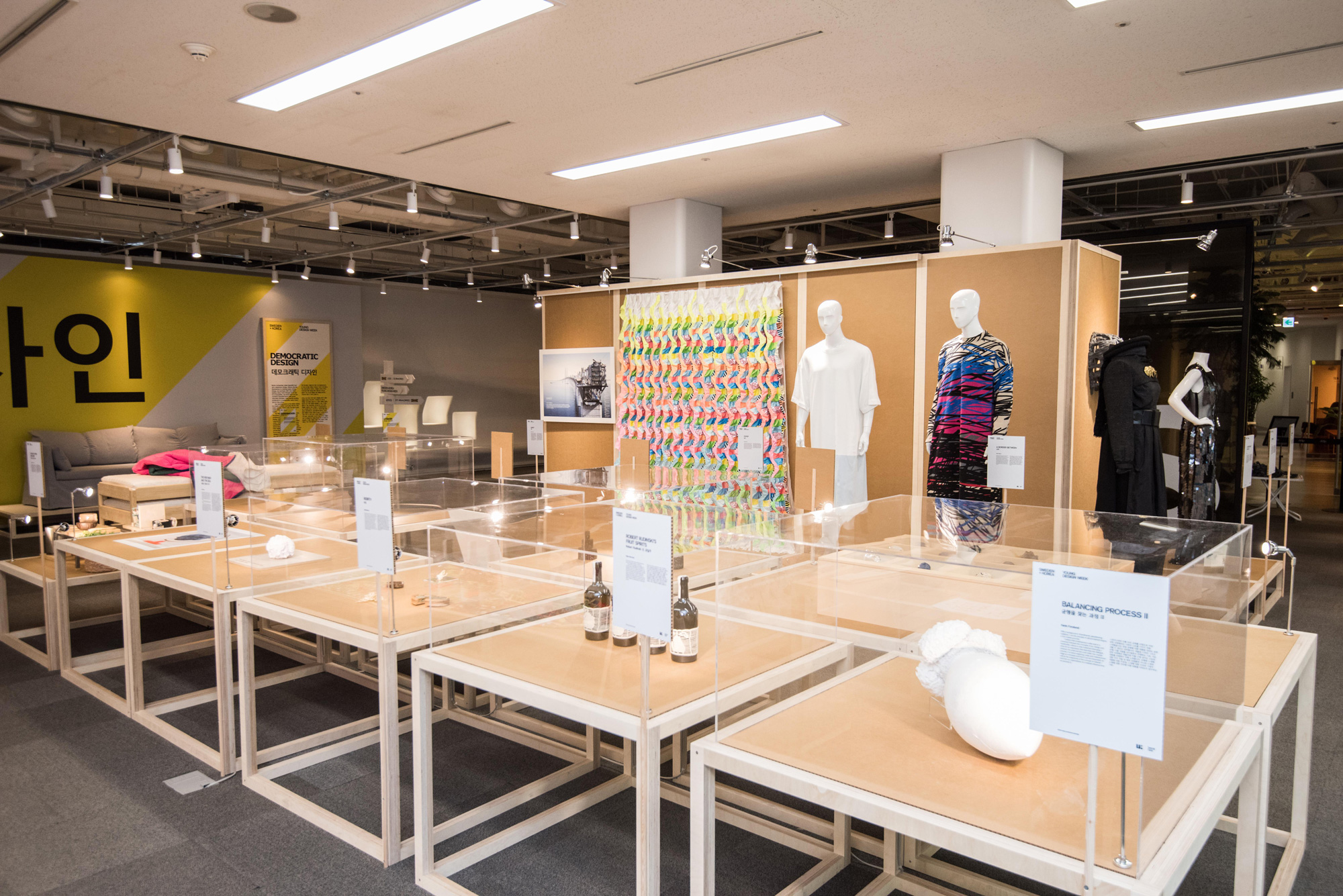 An exhibition space with displays of garments and household items.