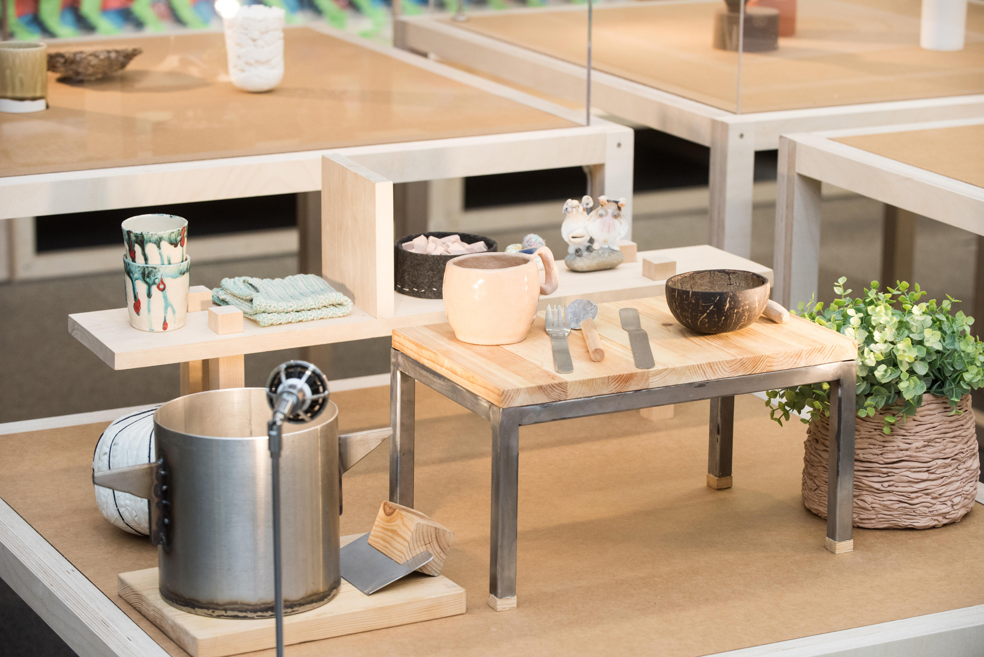 A display of various tableware in an exhibition space.