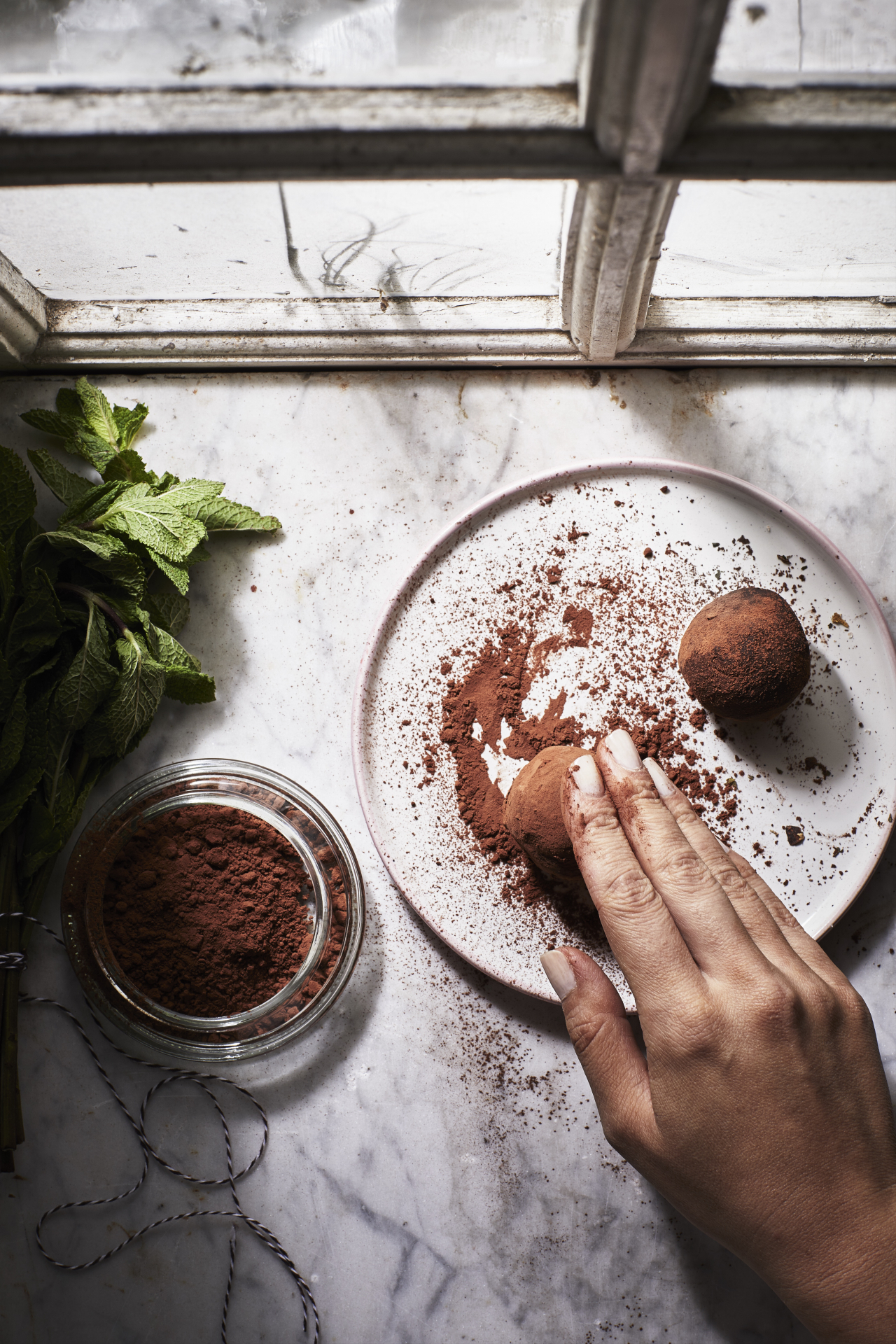 A hand rolling chocolate balls in cocoa powder on a white plate, on a marble worktop by a window.