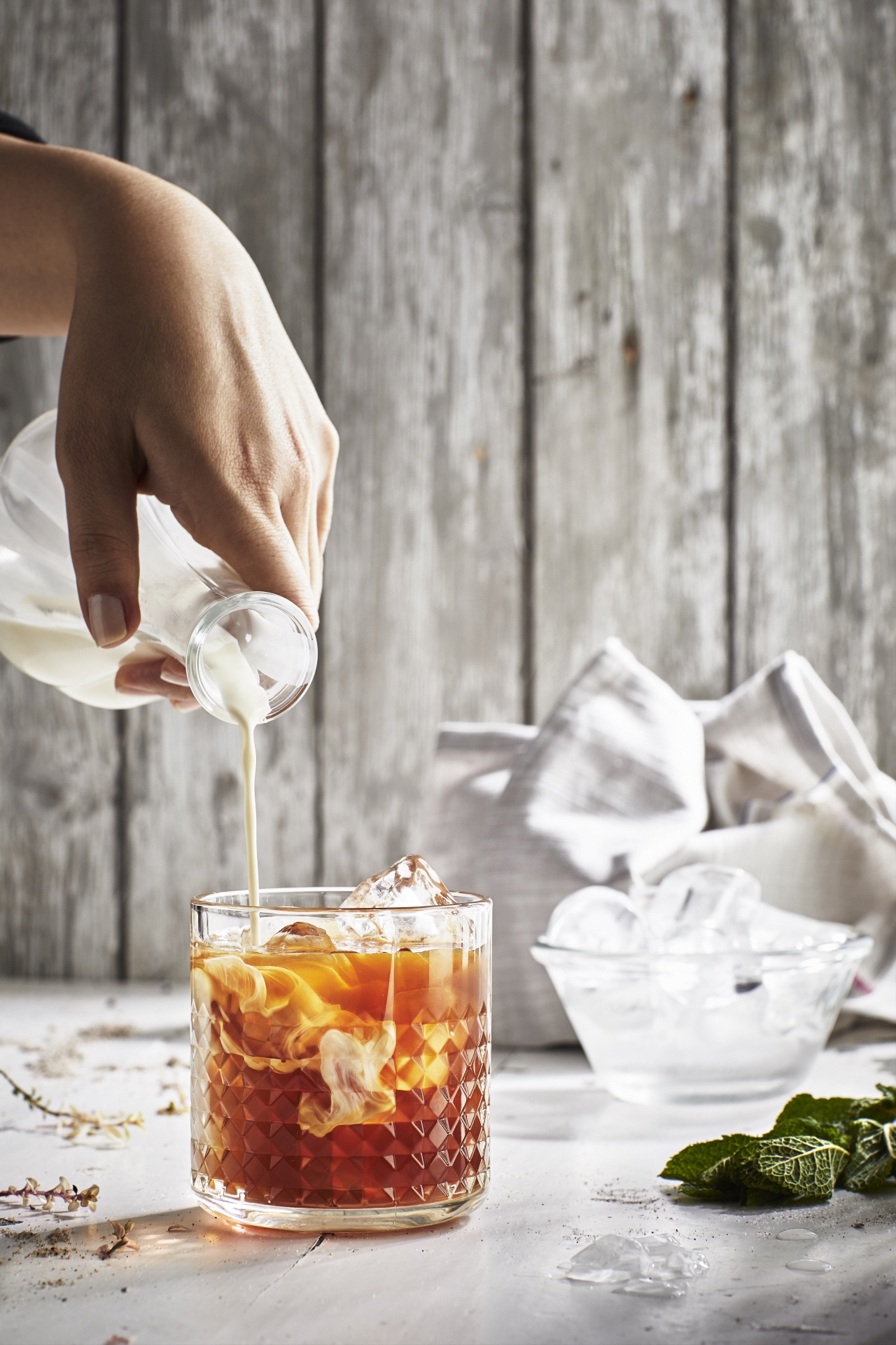 A hand pouring milk into a glass of iced tea, with a bowl of ice and a tea towel in the background.