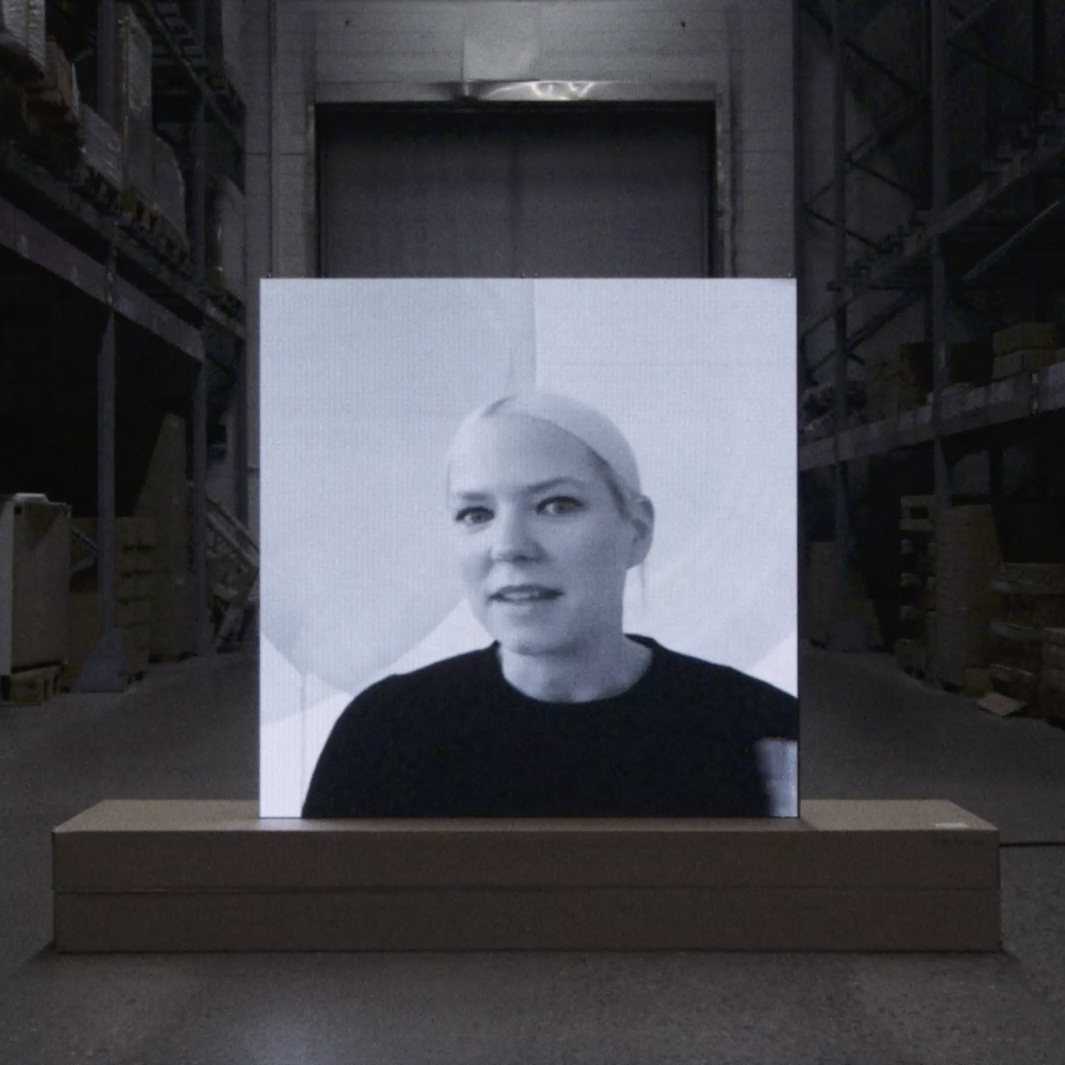 A black-and-white photo print of a blonde woman in a dark sweater, on a brown base in a dark warehouse.