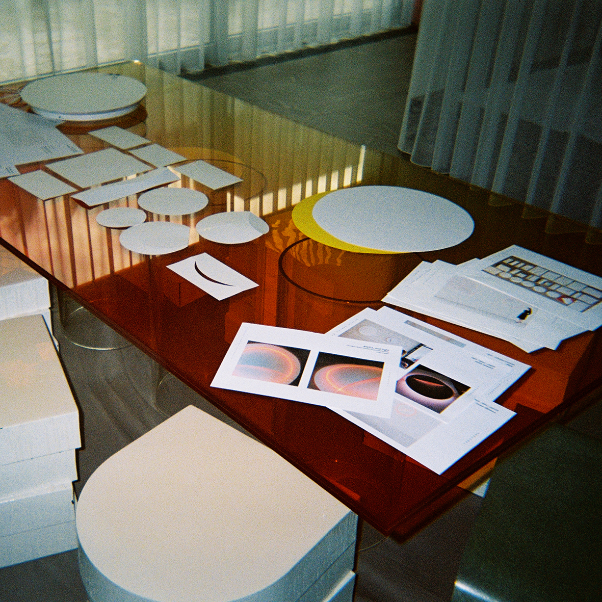 White boxes in piles beside an orange glass table, with a white wall lamp and pieces of paper on top.