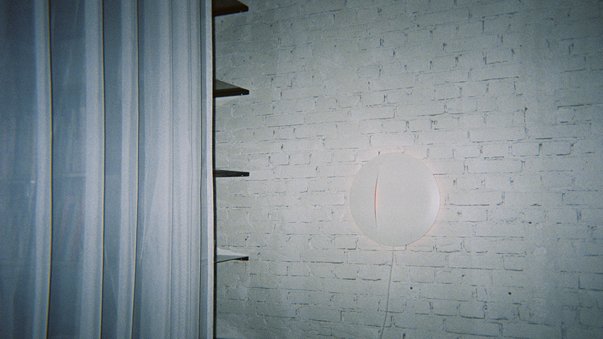 A white round wall lamp on a white brick wall, beside black shelving and a white curtain.