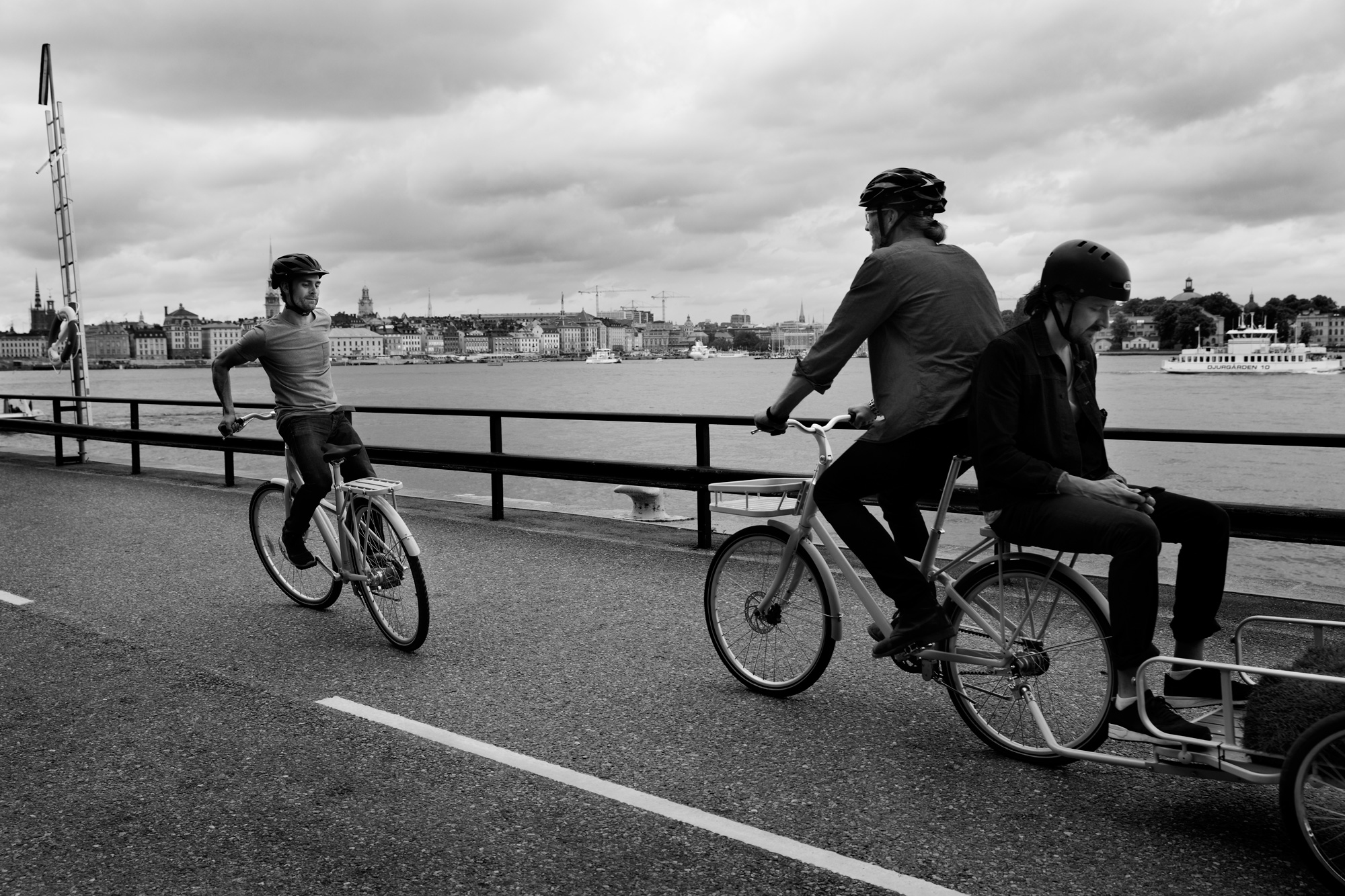On a waterfront road a man is riding a bicycle backwards, closely followed by two men on a bike with a trailer wagon.