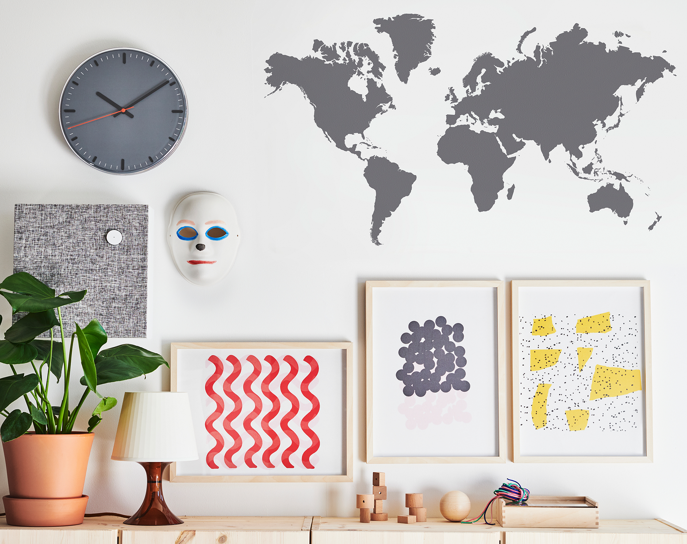 The top of a row of cabinets. Art, a clock, a mask and a world map are on the wall above.