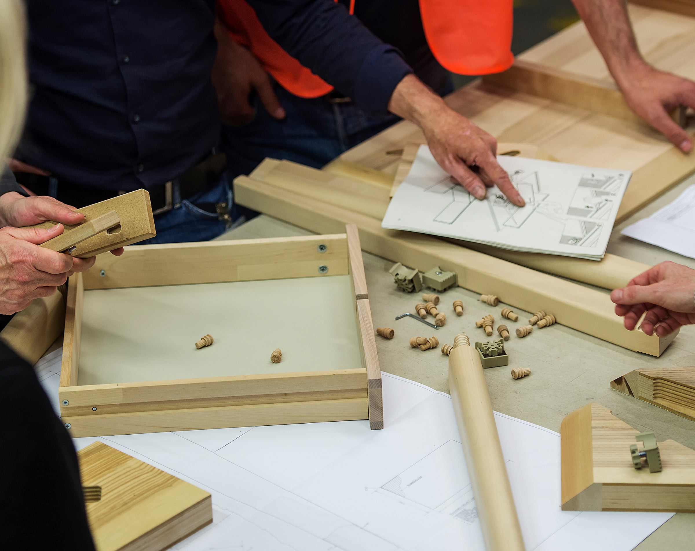 Four people are putting together a piece of IKEA furniture in pale wood using wedge dowels to slot the parts together.