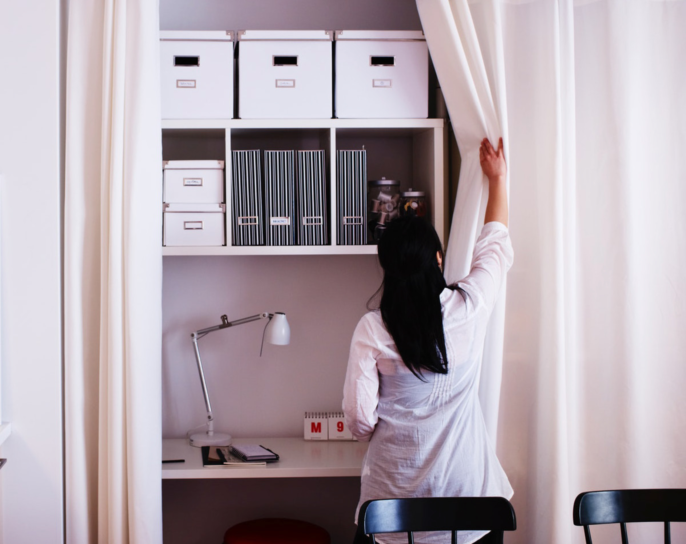 Woman opening a curtain to reveal a neatly organised workspace with IKEA shelving and organisers.