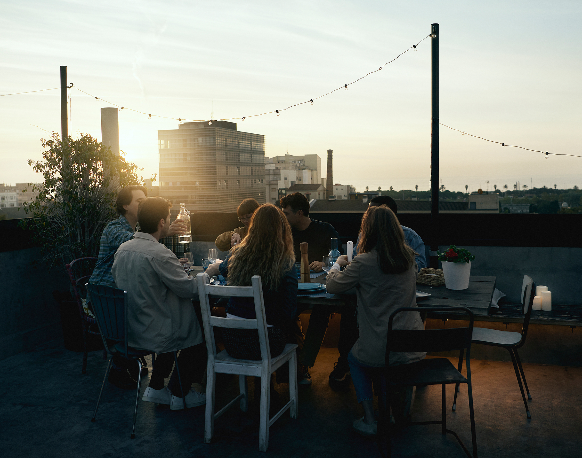 A group of friends is having dinner on a roof top as the sun sets in the city landscape behind.