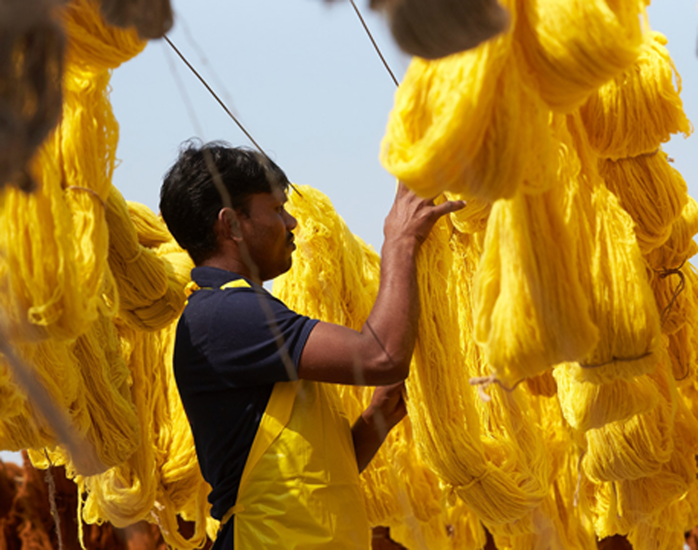 A man in a yellow apron stands in the middle of rows of yellow yarn hung out to dry in the sun.