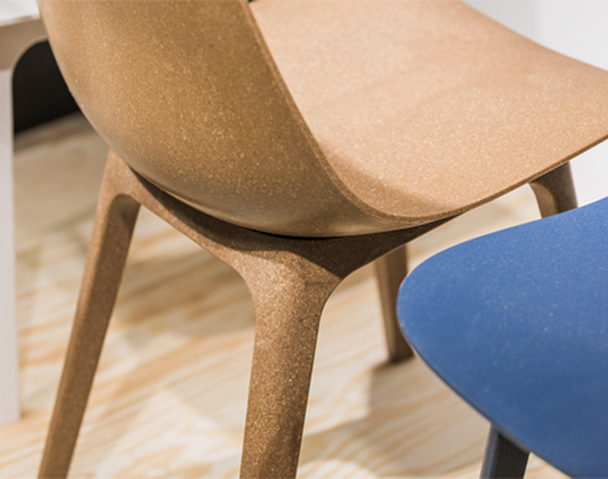 An image of the bowl-shaped seat and rounded back of a brown IKEA ODGER chair made of renewable wood and recycled plastic.