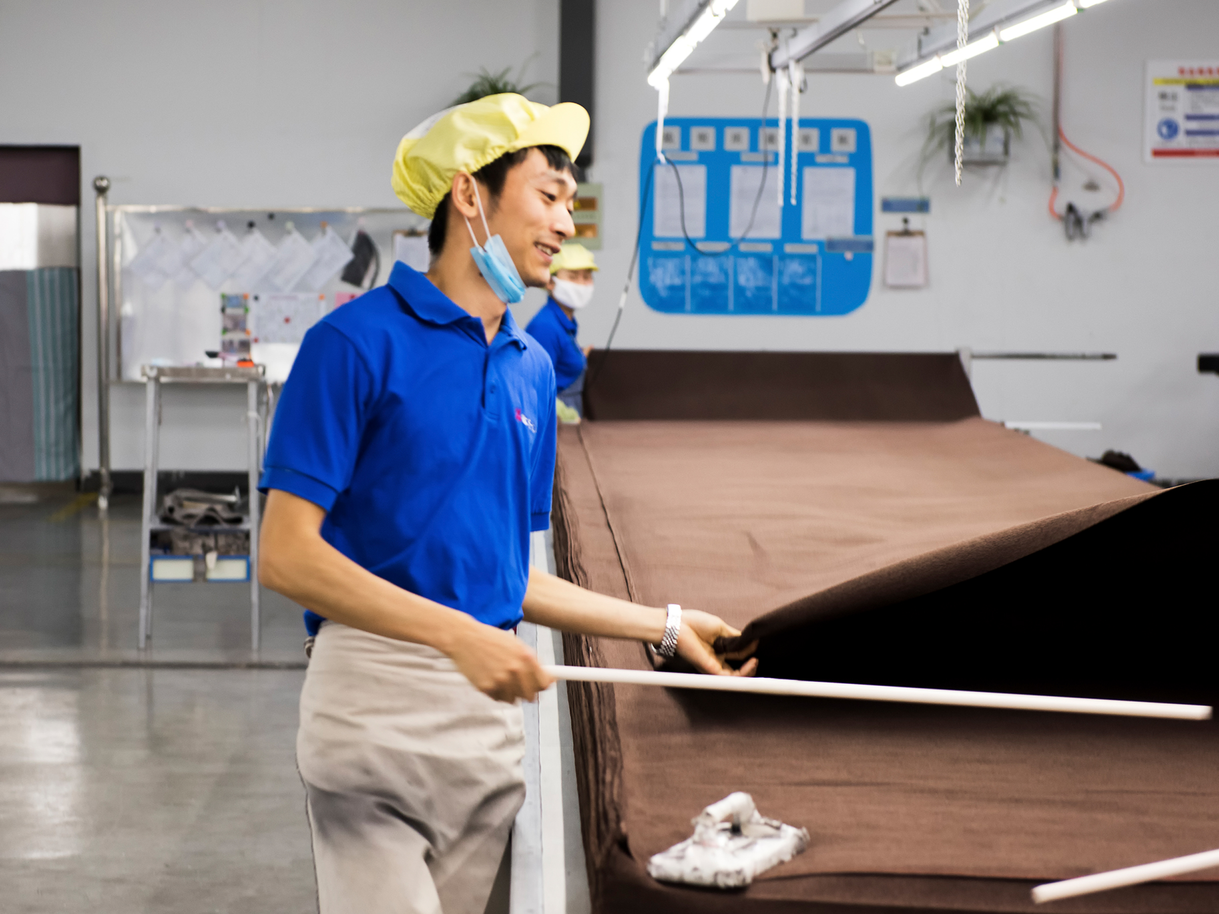 A man wearing a blue shirt, a yellow cap, and a light blue mask is busy working in a factory.