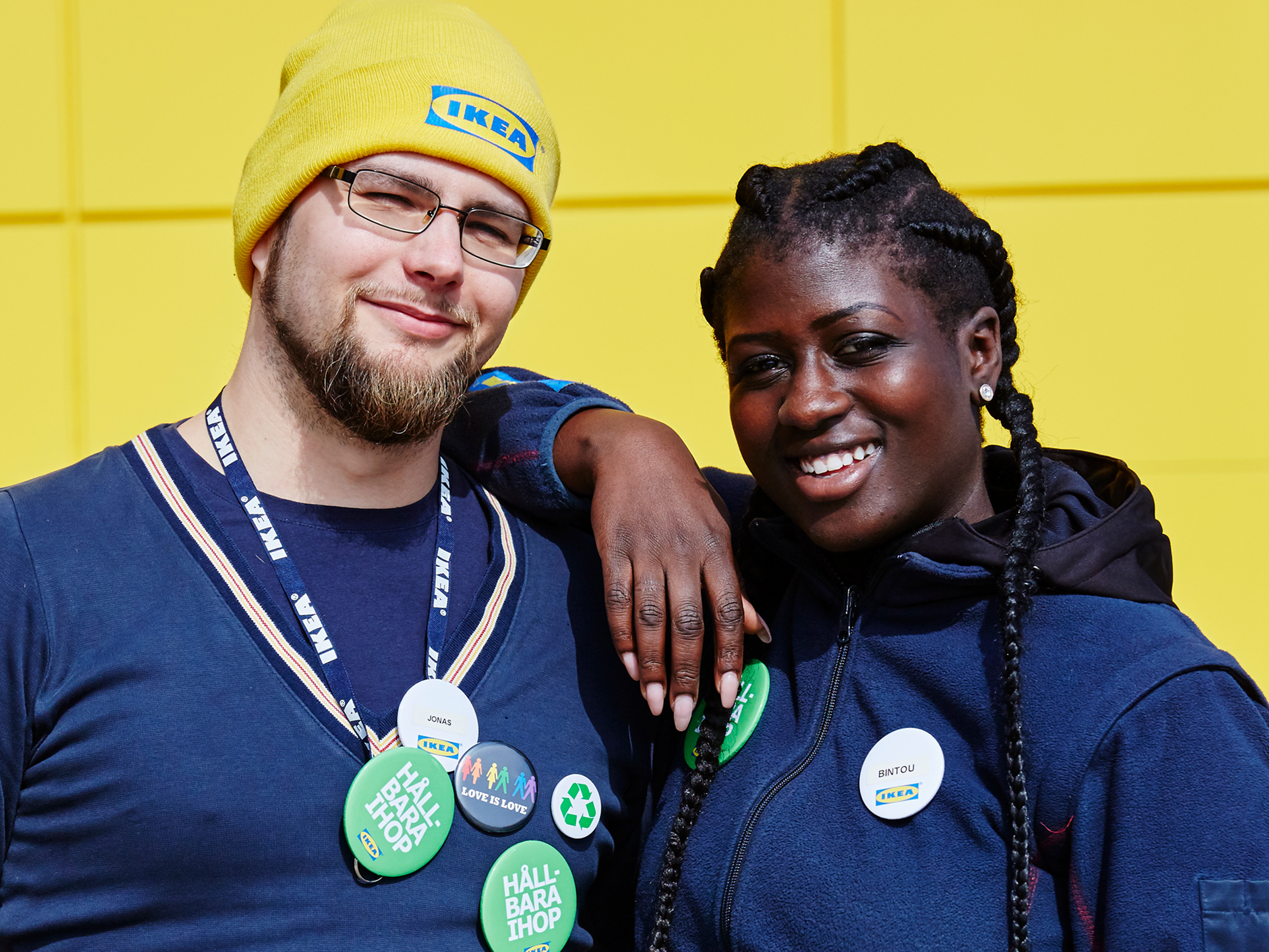 Two IKEA co-workers wearing navy uniforms are standing in front of a yellow wall. They are both smiling.