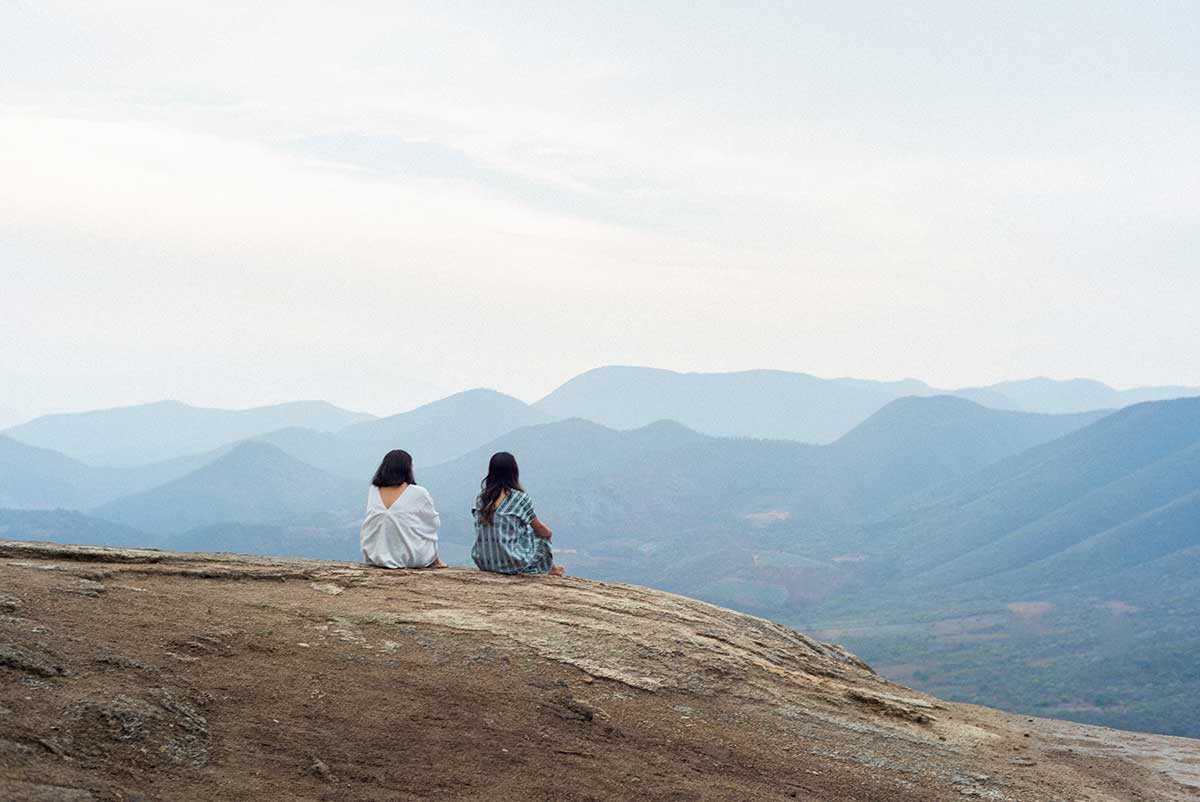 Two people sitting on a mountain looking